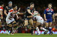 Lloyd Williams of Wales passes the ball while tackled by Kensuke Hatakeyama of Japan. Under Armour 2016 series international rugby, Wales v Japan at the Principality Stadium in Cardiff , South Wales on Saturday 19th November 2016. pic by Andrew Orchard, Andrew Orchard sports photography
