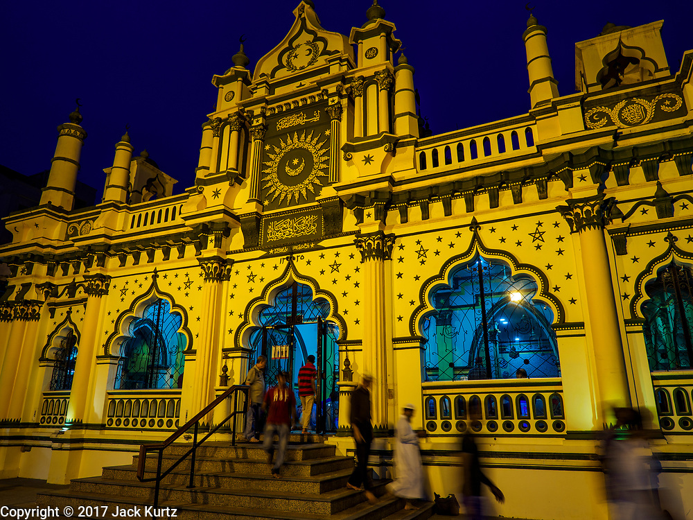 """09 JULY 2017 - SINGAPORE: People leave the Abdul Gaffoor Mosque in Singapore's """"Little India"""" after evening prayers. The mosque is popular with Muslims in Singapore's guest worker community. There are hundreds of thousands of guest workers from the Indian sub-continent in Singapore. Most work 5 ½ to six days per week. On Sundays, the normal day off, they come into Singapore's """"Little India"""" neighborhood to eat, drink, send money home, go to doctors and dentists and socialize. Most of the workers live in dormitory style housing far from central Singapore and Sunday is the only day they have away from their job sites. Most work in blue collar fields, like construction or as laborers.    PHOTO BY JACK KURTZ"""