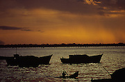 Silhoueted man drives a canoe at sunset, in the fishing harbour in Ilha de Mozambique