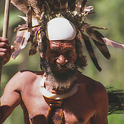 Tribal shaman and medicine man from a village near Kundiawa in the Papua New Guinea Highlands. Wearing a fabulous head-dress of shell and feathers.