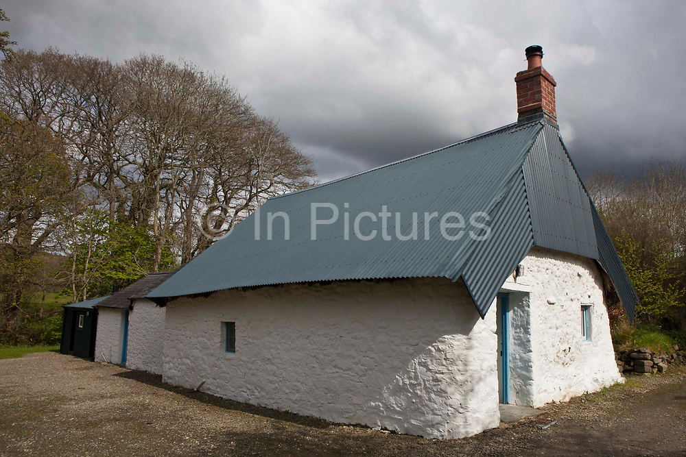 An example of an early 17th-century cottage, built of stone and clom (a mixture of clay, horse hair, and cow dung). Originally thatched, it is now fitted with a corrugated tin roof to save having to maintain straw thatching.  Llanerchaeron House has several holiday cottages in the grounds, their energy saving changes include extra insulation and biomass boilers. Here is an early 17th-century Clom (mud constructed walls), stone and thatch cottage, nowadays with a corrugated tin roof. The National Trust has cut energy use in its Wales region by a massive 41% over just two years, demonstrating that even the most sensitive buildings can be made much more energy efficient. Secrets of success include a combination of efficiency measures, sustainable heating technologies and culture change. As well as cutting down on energy use it has also installed renewable sources of energy, including solar PV and hydro power.