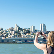 Tourists on a boat cruise taking photos of San Francisco