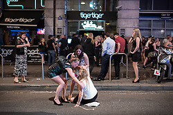 © Licensed to London News Pictures . 15/06/2014 . Manchester , UK . A woman falls in the road in front of Tiger Tiger . People on a night out in Manchester City Centre overnight , following England's defeat to Italy in the World Cup . Photo credit : Joel Goodman/LNP