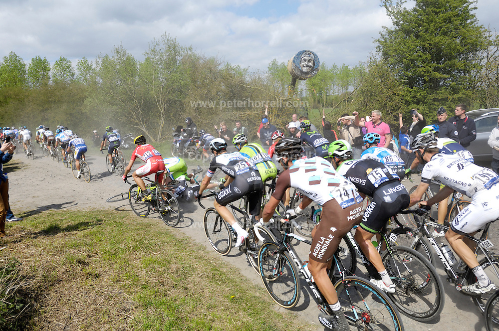 France, April 13th 2014: Overlooked by an image of a smiling Gilbert Duclos Lasalle painted on a straw bale, an unidentified Cannondale rider crashes into an unidentified Orica GreenEdge rider on the pave near Pont Gibus during the 2014 Paris Roubaix cycle race.