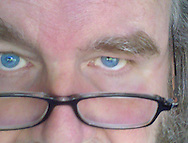 a mature man looks at the camera with his blue eyes above his reading glasses - partial face
