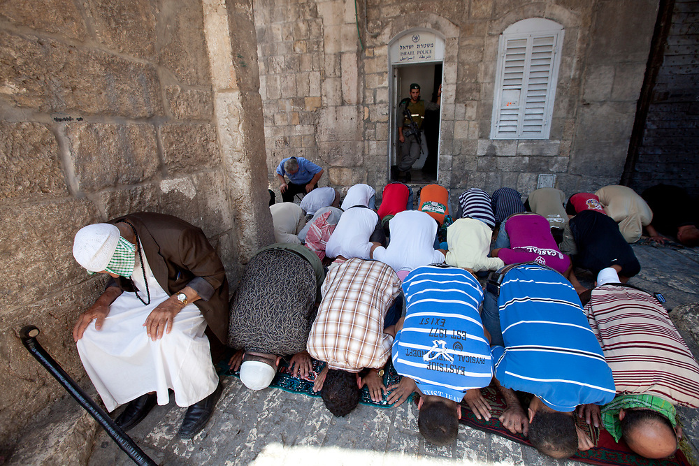 Muslim worshippers pray, as an Israeli border policeman  watches over, at one of the entrances to the Al Aqsa Mosque compound on the second Friday of the Muslim holy month of Ramadan, August 20, 2010.