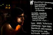 """Retrato de Juan Huq Kutinski (20) conocido como """"Rumi Maki"""" que significa """"Mano de Piedra"""" junto a una de sus letras en quechua. Nació en Calca, en el Valle Sagrado de los Incas. Juan es quechua hablante y desde hace 5 años se dedica al rap, sus letras se enfocan en el regreso al trabajo en la tierra. Juan trabaja produciendo y vendiendo """"Tamales"""" que está hecho a base de maíz. Reparte sus tamales por todo el valle sagrado, él cuenta que esta actividad es una forma de expandir su mensaje, y siempre que vende sus productos, lo hace cantando y tiene más acogida sobre todo de los niños. Cusco, 2020."""