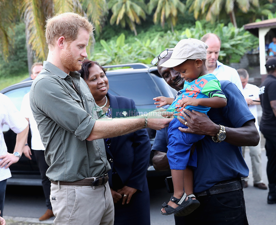 Prince Harry meets Jyasi Junior Nash, two, during a visit to a Turtle Conservation Project at Colonarie Beach, Saint Vincent and the Grenadines, during the second leg of his Caribbean tour.