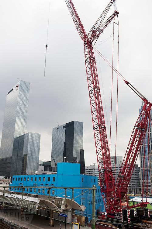 Een grote hijskraan aan het werk bij de bouwput op Rotterdam Centraal Station