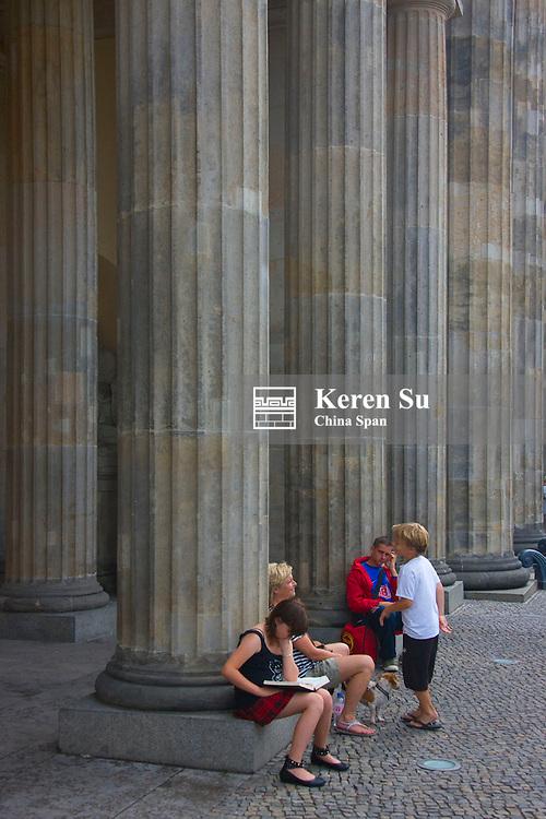 Touristis by the columns of Brandenburg Gate, Berlin, Germany