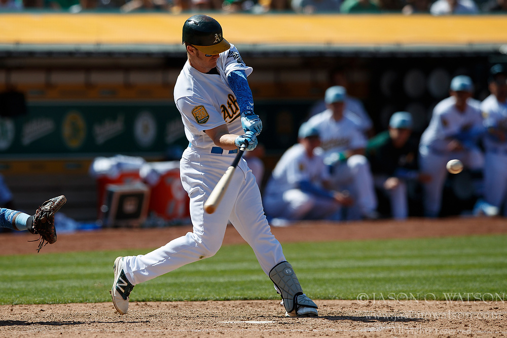 OAKLAND, CA - JUNE 17:  Mark Canha #20 of the Oakland Athletics hits an RBI single against the Los Angeles Angels of Anaheim during the ninth inning at the Oakland Coliseum on June 17, 2018 in Oakland, California. The Oakland Athletics defeated the Los Angeles Angels of Anaheim 6-5 in 11 innings. (Photo by Jason O. Watson/Getty Images) *** Local Caption *** Mark Canha
