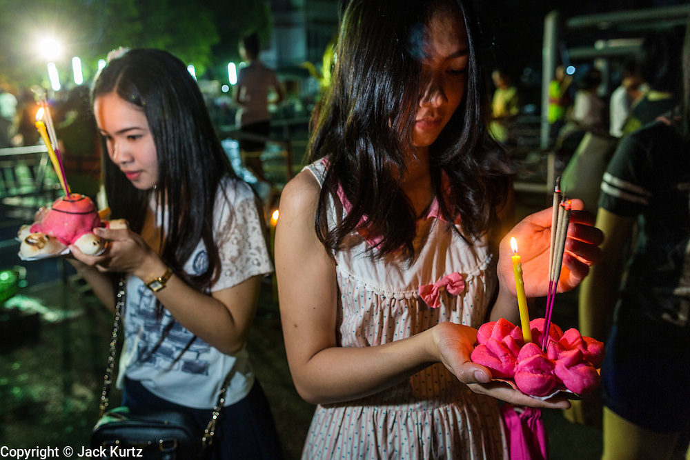 "17 NOVEMBER 2013 - BANGKOK, THAILAND: Women pray before floating their krathongs in the Chao Phraya River near Wat Yannawa in Bangkok. Loy Krathong (also written as Loi Krathong) is celebrated annually throughout Thailand and certain parts of Laos and Burma (in Shan State). The name could be translated ""Floating Crown"" or ""Floating Decoration"" and comes from the tradition of making buoyant decorations which are then floated on a river. Loi Krathong takes place on the evening of the full moon of the 12th month in the traditional and they do this all evening on the 12th month Thai lunar calendar. In the western calendar this usually falls in November. The candle venerates the Buddha with light, while the krathong's floating symbolizes letting go of all one's hatred, anger, and defilements       PHOTO BY JACK KURTZ"