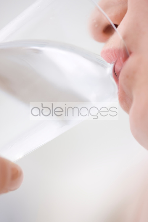Extreme close up of young woman drinking glass of water