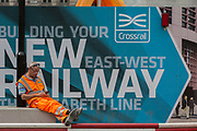 Construction workers rest in front of billboards promoting Crossrail's new Queen Elizabeth rail line, the capital's newest  on 3rd September 2018, at Liverpool Street in London, England. Crossrail's Elizabeth Line is a 118-kilometre (73-mile) railway line under development in London and the home counties of Berkshire, Buckinghamshire and Essex, England. Crossrail is the biggest construction project in Europe and is one of the largest single infrastructure investments ever undertaken in the UK - a£15bn transport project that was due to open in December 2018 but now delayed to autumn 2019.