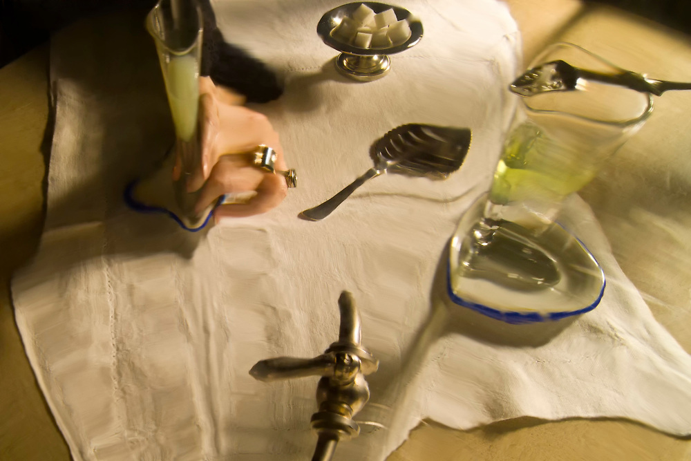 Distorted view from inside a vintage absinthe fountain. The facets of the glass bowl distort the view of the table below. A woman's hand can be seen on the table.