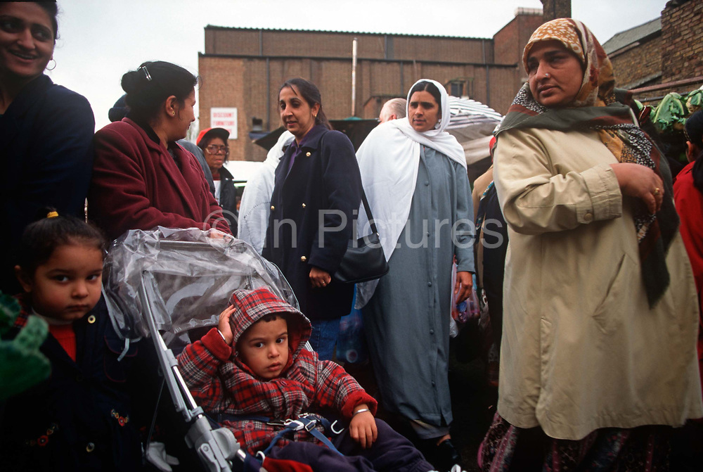 Women and their children populate the daily market in Southall, a West London neighbourhood for the British Asian community, on 16th August 1998, in London, England.