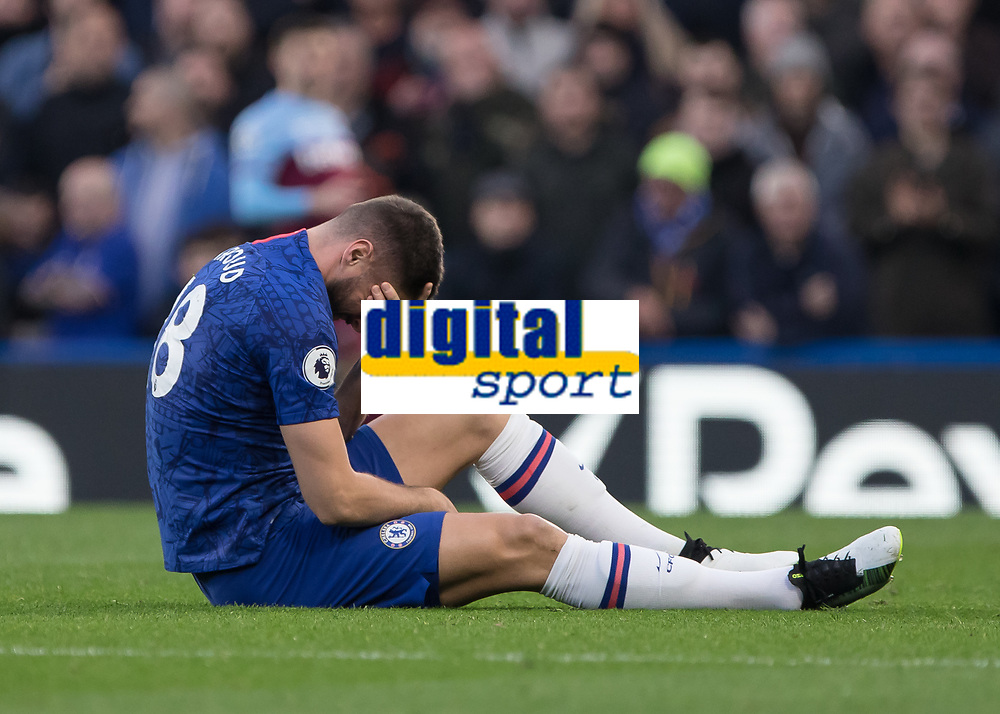 Football - 2019 / 2020 Premier League - Chelsea vs. West Ham United<br /> <br /> Olivier Giroud (Chelsea FC) sits on the ground holdin his head after an early battle with West Ham at Stamford Bridge <br /> <br /> COLORSPORT/DANIEL BEARHAM