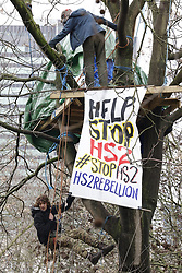 © Licensed to London News Pictures. 28/01/2021. London, UK. A protestor dangles from a tree next to a banner. A group of HS2 Rebellion protesters in Euston Square Gardens are resisting a police operation to remove them. This is the second day of action by police and bailiffs to remove protestors from a square in front of Euston Station. It is reported the protesters have built a 100ft tunnel under the gardens. Photo credit: Peter Macdiarmid/LNP