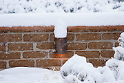 Adobe wall with light in snow in New Mexico.