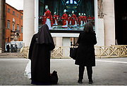 A nun and a woman watch the pre-conclave mass in St. Peter's Basilica in St. Peter's Square during the first day of conclave and the selection of the new Pope in Vatican City, March 12, 2013. Photograph by Todd Korol