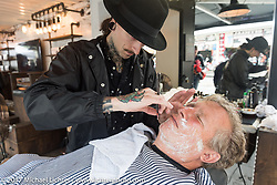 Charlie St. Clair gets a shave in the Progressive Insurance booth on Lakeside Avenue on a rainy day in Weirs Beach during Laconia Motorcycle Week, New Hampshire, USA. Friday June 16, 2017. Photography ©2017 Michael Lichter.
