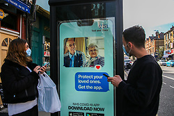 "© Licensed to London News Pictures. 26/09/2020. London, UK. A couple wearing face masks download the NHS Track and Trace app on their mobile phones while standing next to 'Protect your loved ones. Get the App' digital advert in north London, which is a part of the government's new public information campaign. The app was launched early this week after months of delay and questions about its effectiveness. Health Secretary MATT HANCOCK said that, ""Every single person who downloads the app is helping to improve how it can keep us safe. It helps you to keep yourself and your loved ones safe."" Users who have tested negative for COVID-19 are unable to input and share the results on the NHS app, if they did not book the test via the app in the first place. Photo credit: Dinendra Haria/LNP"