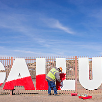 """021214       Cable Hoover<br /> <br /> Odion Garcia from the City of Gallup Parks Department paints a red swatch on the Gallup sign on Historic Highway 66 near downtown Wednesday. The sign will now have an American flag theme to match Gallup's """"Most Patriotic"""" status."""