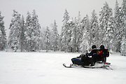 A group of travelles on snowmobiles