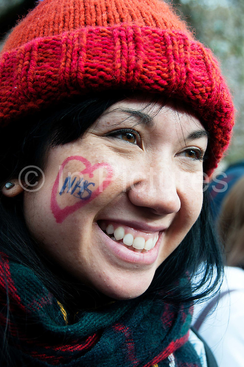 Tens of thousands of health workers, activists and members of the public protested against austerity and cuts in the NHS National Health Service on March 4th 2017 in London, United Kingdom. A healthworker has a heart drawn on her cheek with NHS written inside it,