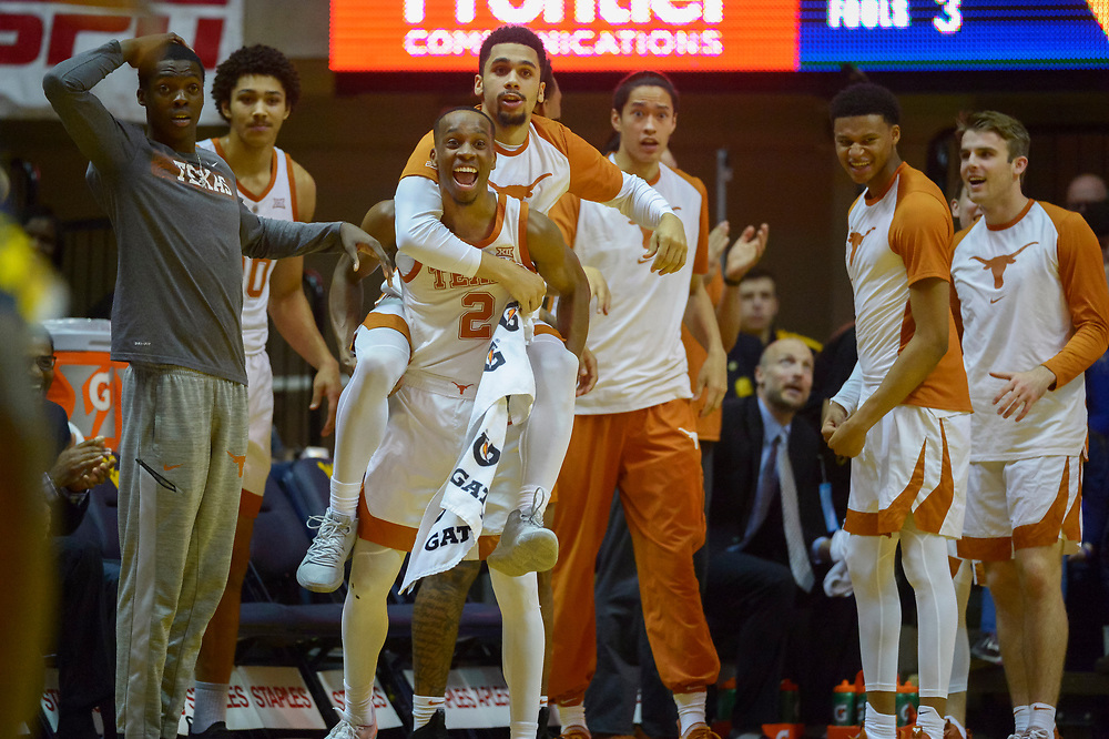 Teammates react after another slam dunk from Texas Longhorns forward Jericho Sims (20) during the second half of an NCAA college basketball game in Morgantown, W.Va. on Saturday Feb. 9, 2019. (AP Photo/Craig Hudson)