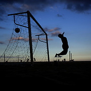 The goalkeeper dives to save a shot during a football match at sunset on Copcabana beach, Rio de Janeiro,  Brazil. 5th July 2010. Photo Tim Clayton..