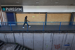 © Licensed to London News Pictures .  07/05/2020 . Salford, UK. A man walks past a boarded up branch of Pure Gym at Salford Shopping Precinct . Photo credit : Joel Goodman/LNP