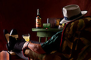 A smartly dressed man enjoying an end of the day Herbsaint cocktail while listening to music