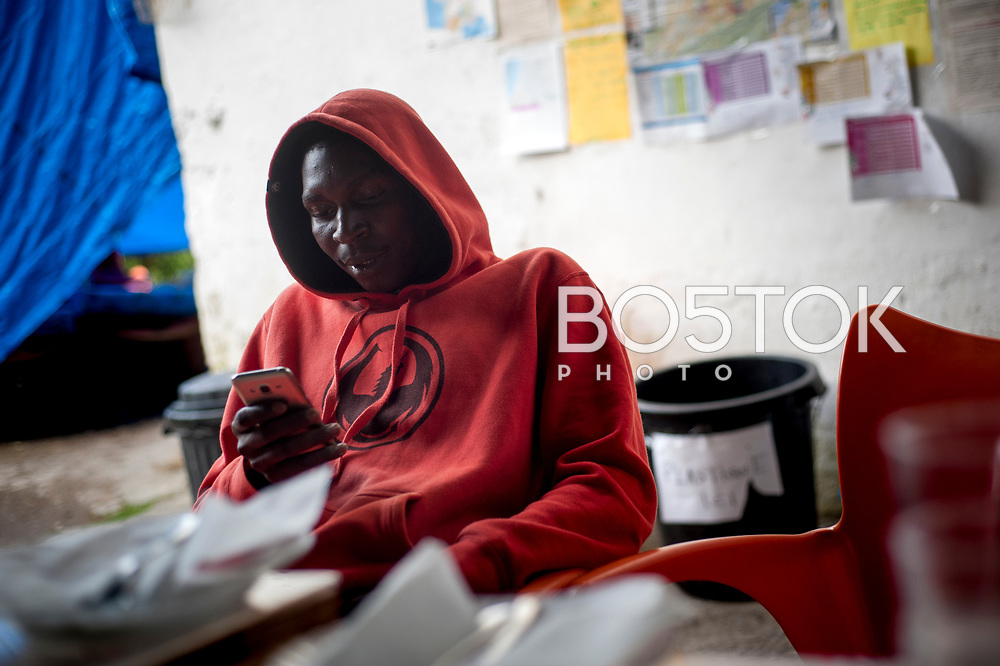 An African migrant attends his smartphone in Lakaxita. Irun (Basque Country). August 30, 2018. Lakaxita is a self-managed socio-cultural space located in an occupied house, where volunteers have created a hosting network for migrants in transit who have already completed the 5-day period that can remain in public resources. This group of volunteers is avoiding a serious humanitarian problem Irún, the Basque municipality on the border with Hendaye. As the number of migrants arriving on the coasts of southern Spain incresead, more and more migrants are heading north to the border city of Irun. (Gari Garaialde / Bostok Photo)