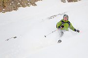Judd MacRae skis down a couloir below Hayden Peak, San Juan Mountains, Colorado, with his face covered in snow.