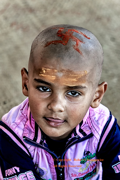 Child of Faith: A young boy proudly wears the red swastika, an ancient symbol of his Hindu faith, Varanasi India.
