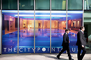 City workers walk past The Citypoint Club a fitness and spa center based in the City of London.