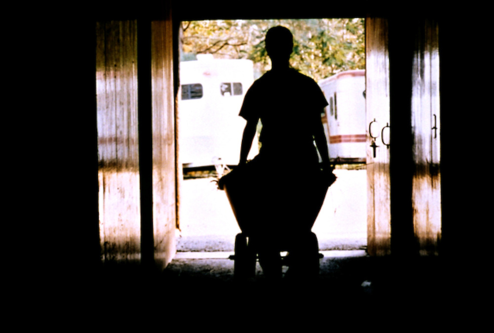 Brightly lit from behind by sunlight, a worker pushes a wheelbarrow into a barn.