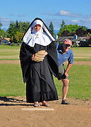 """Humorous photograph of a man standing behing a nun on a pitcher's mound visually depicting the saying """"Second to nun!"""""""