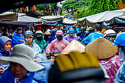 Crowded streets of Hoi An Market area during rainy season.