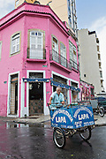 An elderly man rides a bicycle cart selling baked goods in  the Lapa neighborhood of Rio de Janeiro, Brazil.