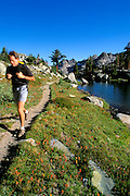 Hiker on trail along the shore of Minaret Lake, Ansel Adams Wilderness, Sierra Nevada Mountains, California