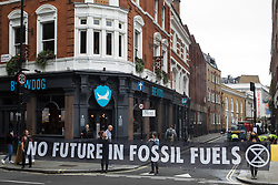 Environmental activists from Extinction Rebellion hold a banner reading No Future In Fossil Fuels during the first day of Impossible Rebellion protests on 23rd August 2021 in London, United Kingdom. Extinction Rebellion are calling on the UK government to cease all new fossil fuel investment with immediate effect. (photo by Mark Kerrison/In Pictures via Getty Images)