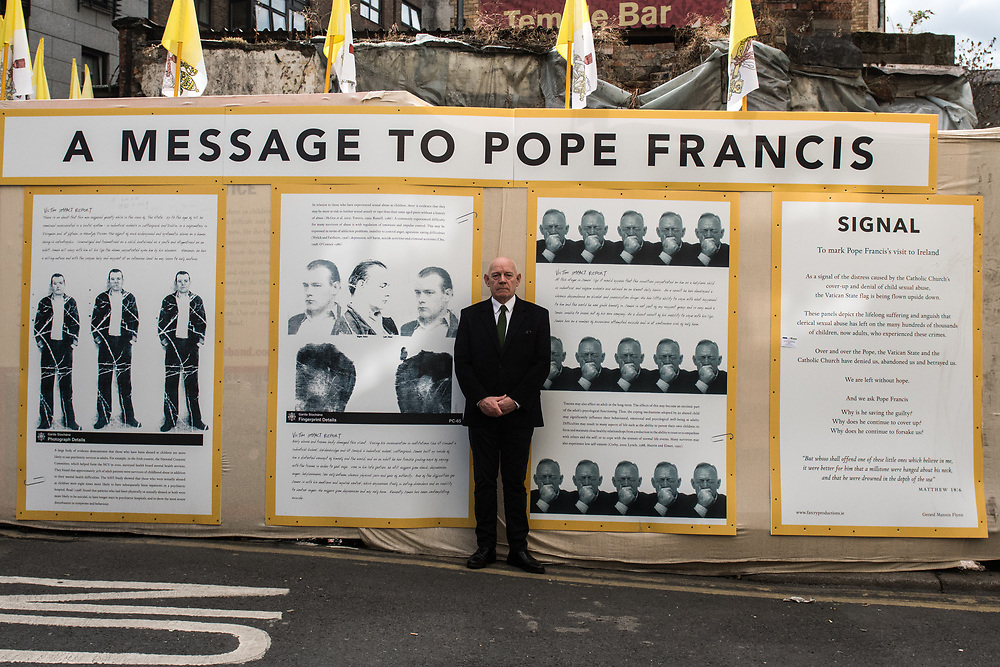 """Dublin, Ireland. 25th August, 2018. <br /> Dublin City Council Councillor and artist Mannix Flynn, also an Irish survivor, abused by clergy, poses in front of his installation during the first of the two-days of the visit of Pope Francis in Dublin, Ireland.<br /> Pope Francis has made a two-day visit to the Republic of Ireland by celebrating a Mass at Dublin's Phoenix Park. The Argentine Pope asked forgiveness for the """"abuses in Ireland, abuses of power, conscience and sexual abuses"""" perpetrated by Church leaders. It was the first papal visit to Ireland for 39 years. During his activities many activists, victims and survivors have made protests and a silent march Garden of Remembrance towards the last Magdalene Laundry to close in Ireland.<br />  © Simone Padovani"""