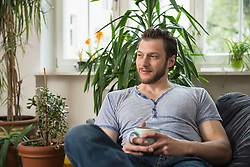 Thoughtful mid adult man drinking coffee in living room and thinking, Munich, Bavaria, Germany