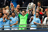 Ederson Moraes (31) of Manchester City holds the FA Cup up in the royal box with Riyad Mahrez (26) of Manchester City and Bernardo Silva (20) of Manchester City during the The FA Cup Final match between Manchester City and Watford at Wembley Stadium, London, England on 18 May 2019.
