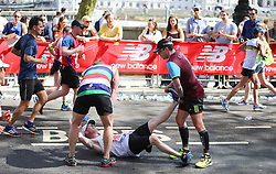 © Licensed to London News Pictures. 22/04/2018. London, UK. A man with cramp is given assistance by other runner during the 2018 London Marathon which is being run in unusually warm temperatures for April. This years event is being started by HRH Queen Elizabeth II. Photo credit: Tom Nicholson/LNP