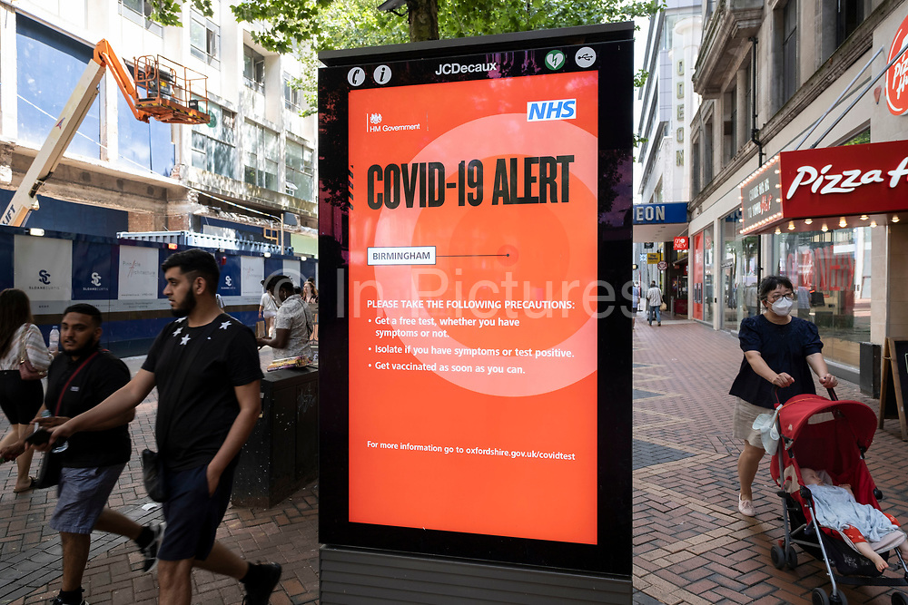People pass a new Covid-19 Alert Public Health England, NHS information board on New Street in what was a positive atmosphere on the long awaited freedom day when all remaining coronavirus restrictions are lifted in the UK on 19th July 2021 in Birmingham, United Kingdom. While many people are wearing face masks, they are no longer mandatory, while government advice suggests that it is advised to wear a face covering in busy public places inside and on transport.