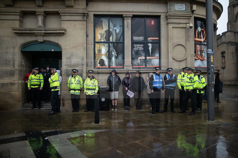 © Licensed to London News Pictures. 31/08/2019. Manchester, UK. Police take shelter in front of the Corn Exchange in Cathedral Gardens during a heavy downpour as a pro EU demo takes place in Manchester City Centre . Objections are raised to the Prime Minister Boris Johnson's intention to prorogue Parliament in the run up to Britain's planned Brexit deadline . Photo credit: Joel Goodman/LNP