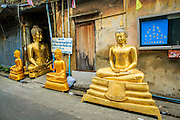 """12 NOVEMBER 2012 - BANGKOK, THAILAND:   Statues of the Buddha for sale on Bamrung Muang Street in Bangkok. Thanon Bamrung Muang (Thanon is Thai for Road or Street) is Bangkok's """"Street of Many Buddhas."""" Like many ancient cities, Bangkok was once a city of artisan's neighborhoods and Bamrung Muang Road, near Bangkok's present day city hall, was once the street where all the country's Buddha statues were made. Now they made in factories on the edge of Bangkok, but Bamrung Muang Road is still where the statues are sold. Once an elephant trail, it was one of the first streets paved in Bangkok. It is the largest center of Buddhist supplies in Thailand. Not just statues but also monk's robes, candles, alms bowls, and pre-configured alms baskets are for sale along both sides of the street.    PHOTO BY JACK KURTZ"""